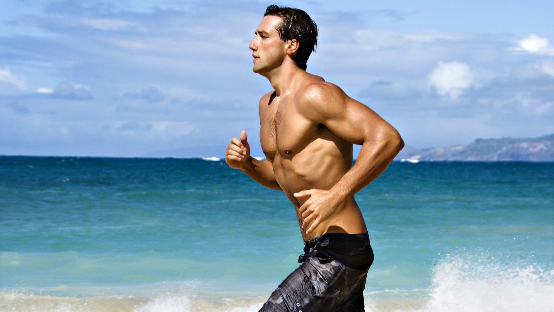 sportsman running on the beach. android wallpapers for free.