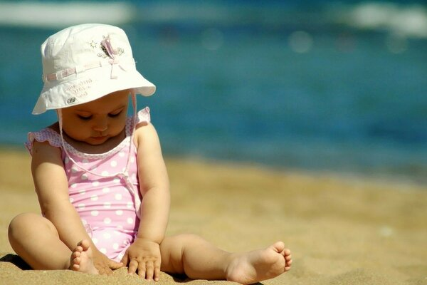 A small child on the beach in the sand