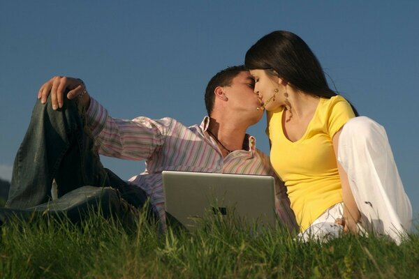 kiss outdoors in front of a laptop