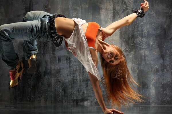 skinny girl in an orange tank top and jeans dancing hip hop