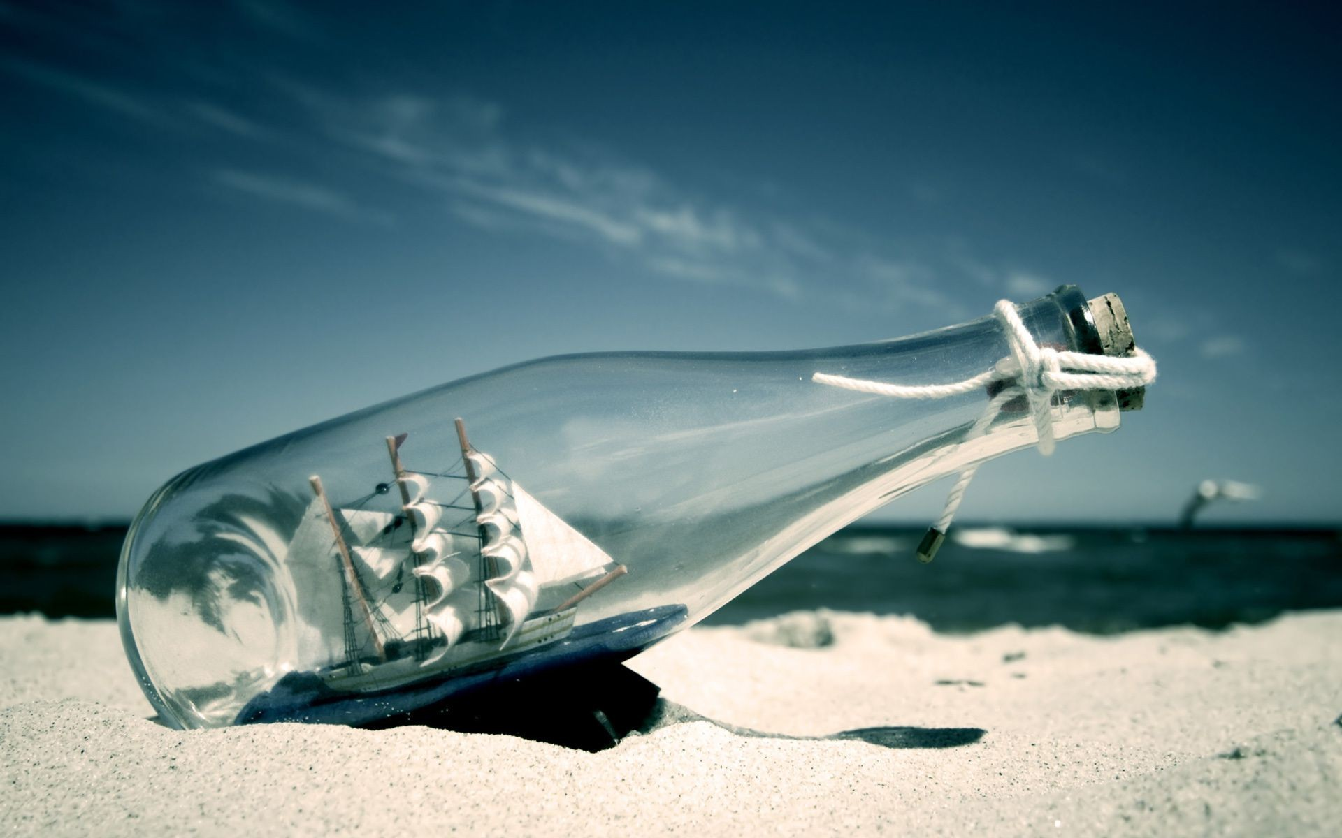 sailboat in a bottle beach sand surf