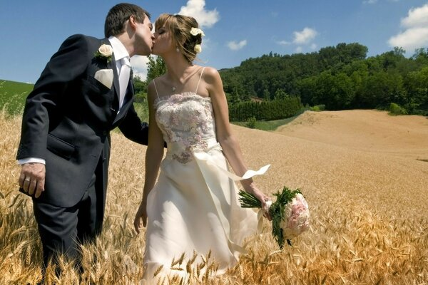 Newlyweds kissing in the middle of the field