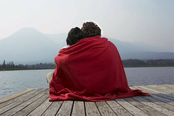 Two lovers on the dock under a red blanket