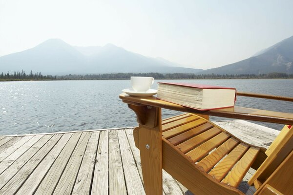 Wooden lounger, coffee mug and a book on the dock