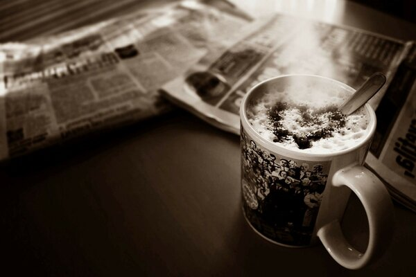 Cup coffee foam heart newspaper table Sepia photo
