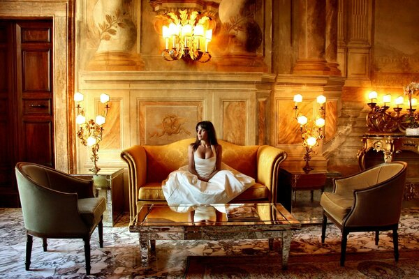 Brunette sitting on the couch in the castle surrounded by lamps