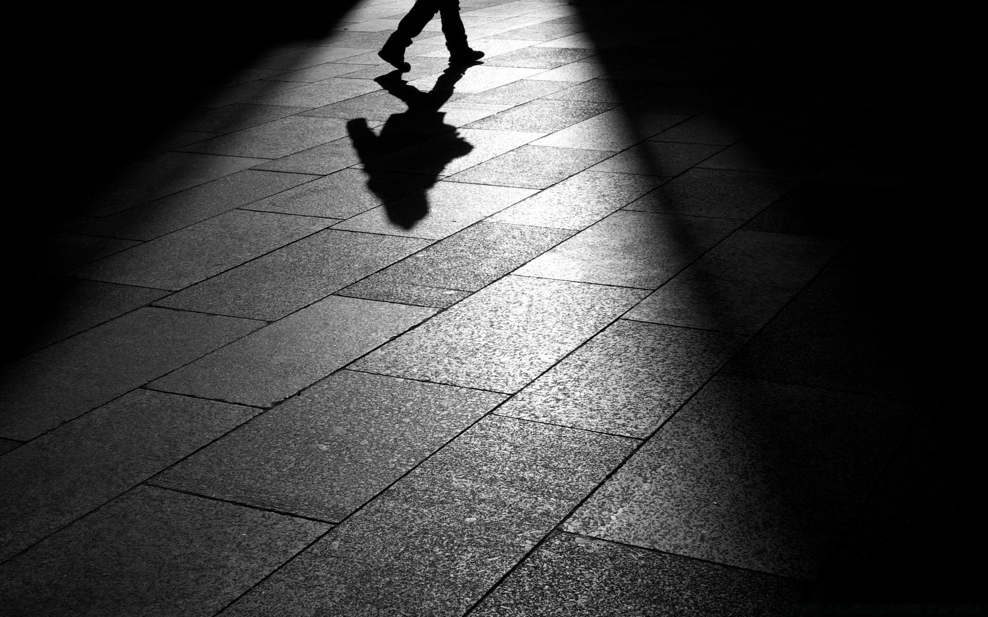 black and white monochrome street shadow pavement dark floor city man blur motion one adult square wall urban abstract