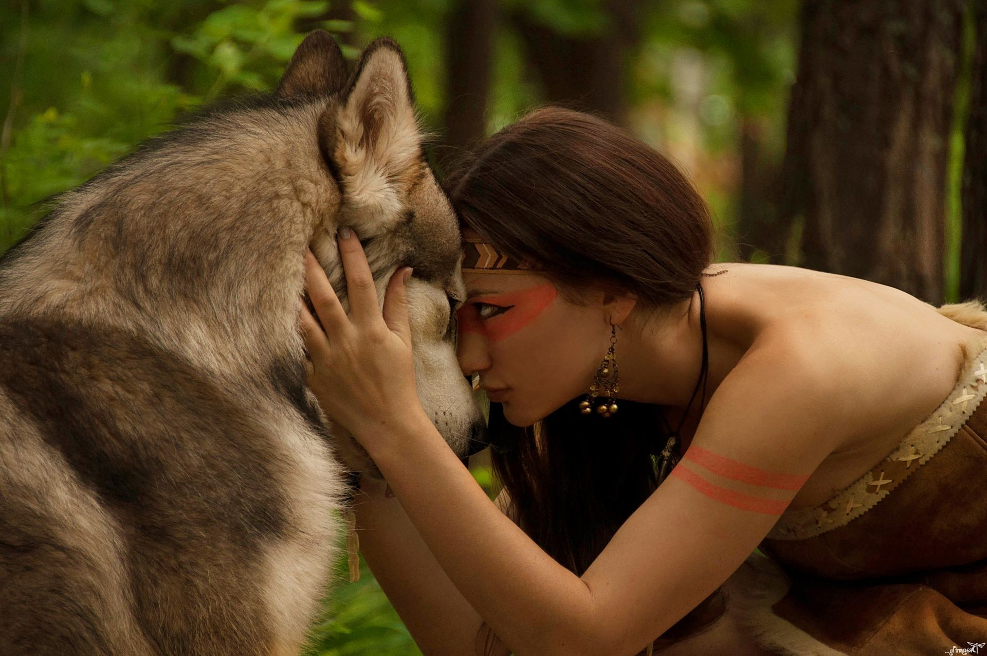 Girl hugging a wolf in the forest