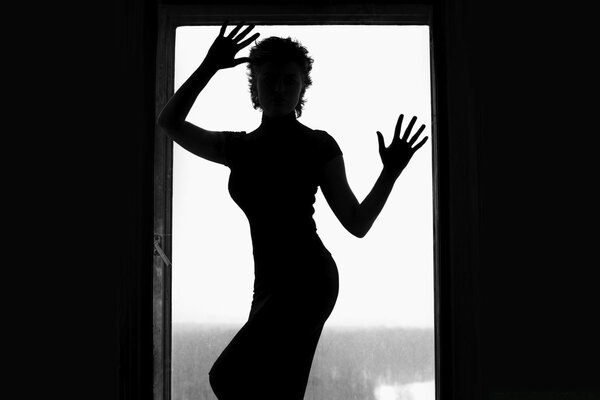 Silhouette Of Woman In Window