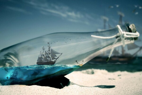 Sea, ship in the bottle and sand