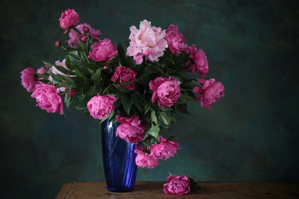 a bouquet of blue Flowers vase of pink peonies