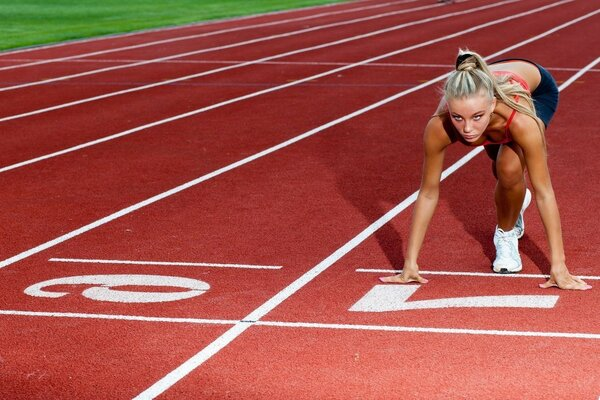 Girl is preparing for the race at 100 meters