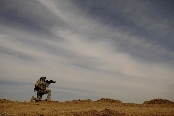 A soldier takes aim at someone in the desert