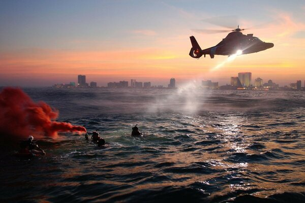 The helicopter performs a rescue operation on the water