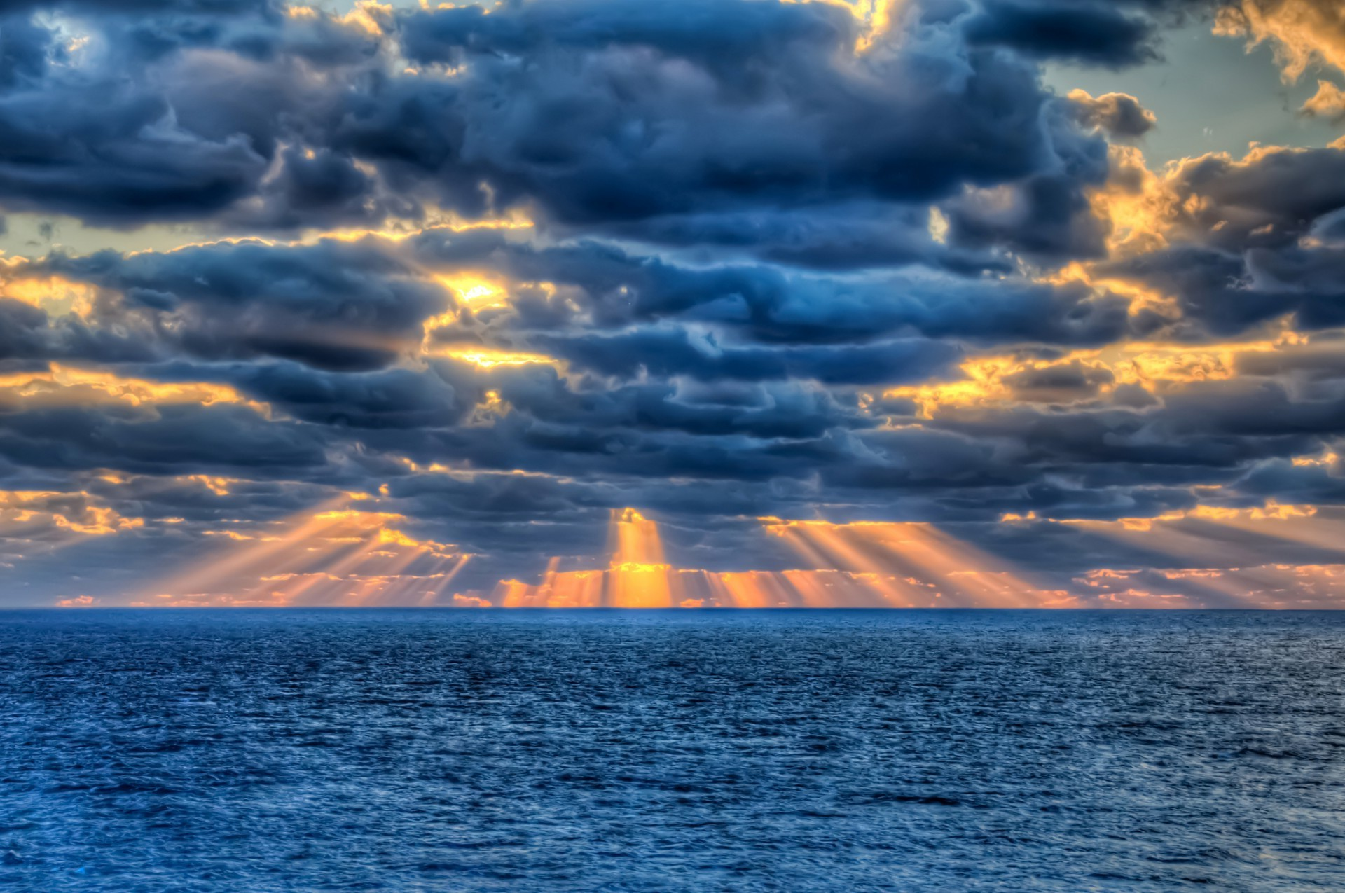 The sun's rays breaking through the clouds over the sea