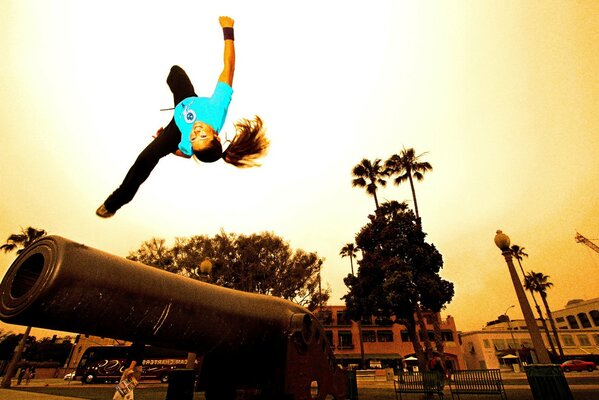 Parkour. She performs a side flip with obstacles
