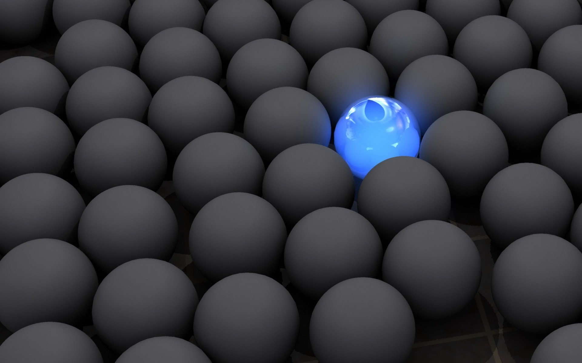 A glowing blue sphere among the masses of the same grey balls