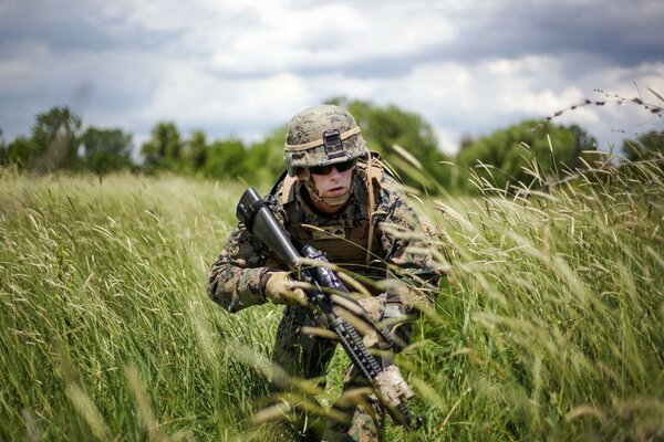 Soldier in uniform sneaking through the tall grass in a field