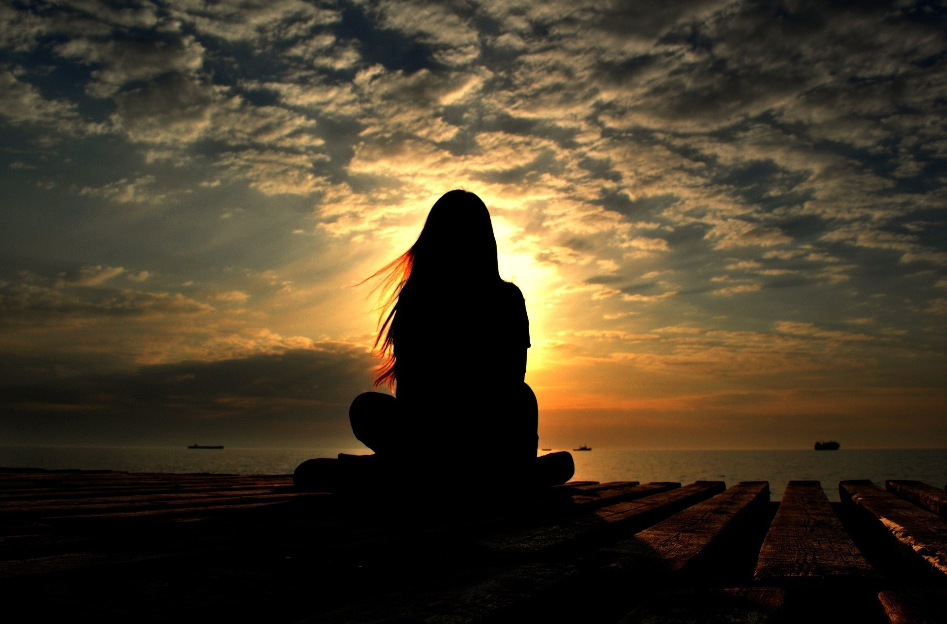 Silhouette of a girl sitting in the Lotus position closed sun
