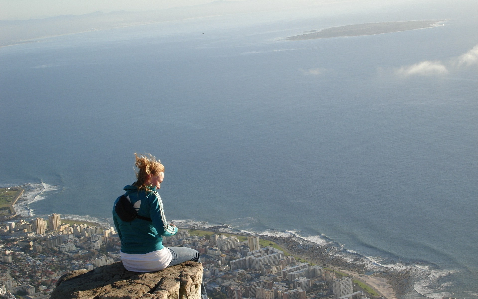 Brave Girl Sitting On The Edge Of A Cliff Above The Town