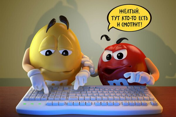 Two candy M&Ms typing on a keyboard