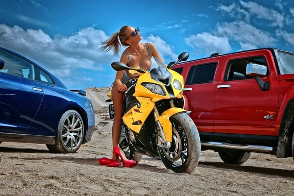 Girl in bikini on a yellow motorcycle in the desert