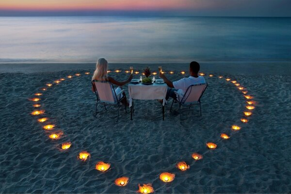 Two lovers for a romantic dinner among candles on the sea