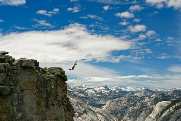 The athlete jumps from a huge cliff down