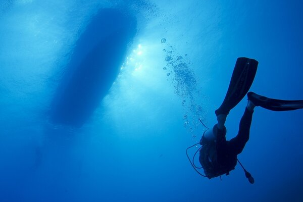 A scuba diver POPs up from the seabed to the boat