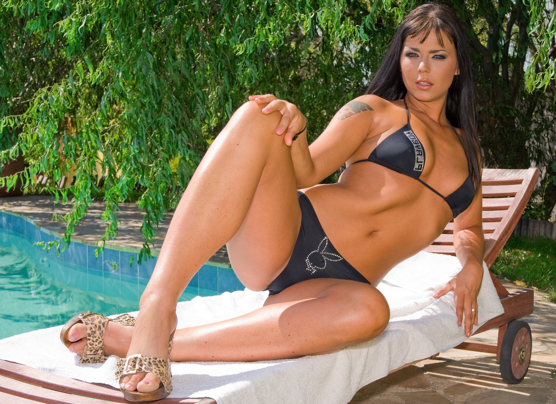 Model Simony Diamond resting on a lounger by the pool