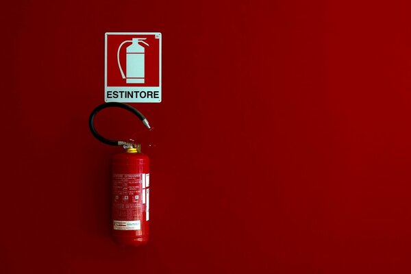 A fire extinguisher on a red background