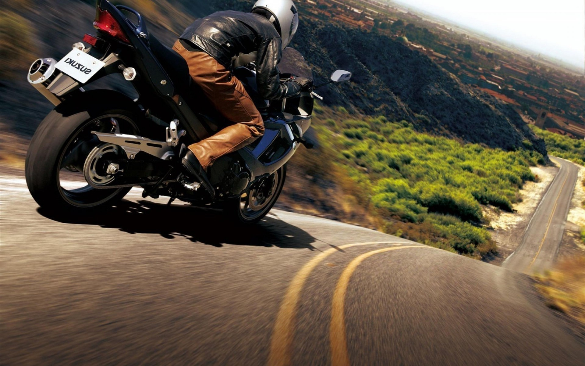 Biker rushes on a motorcycle down the steep slope of the mountain