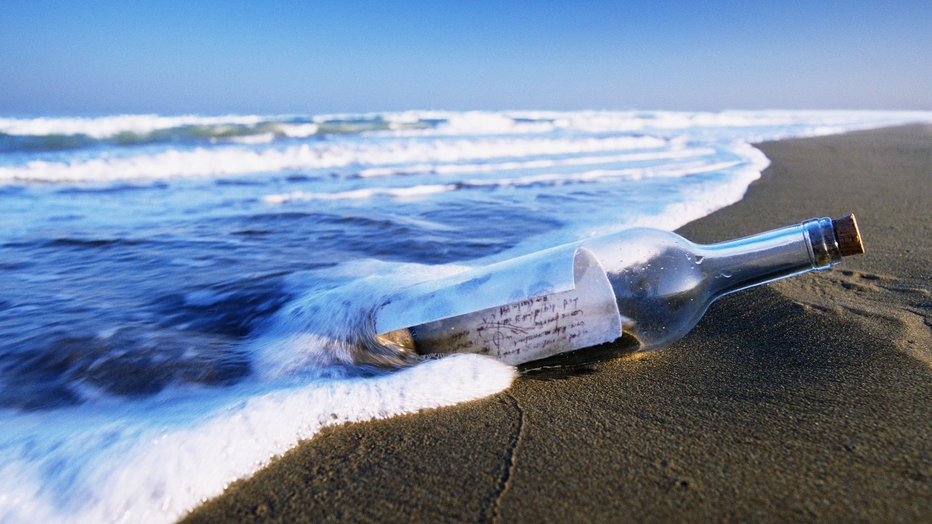 A note in a bottle thrown onto a beach by the sea