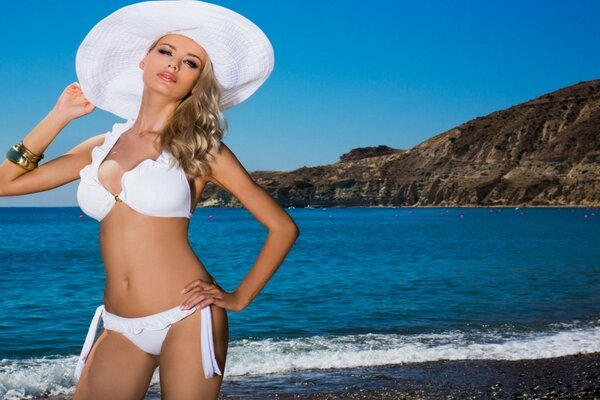 Blonde in white hat on the shore