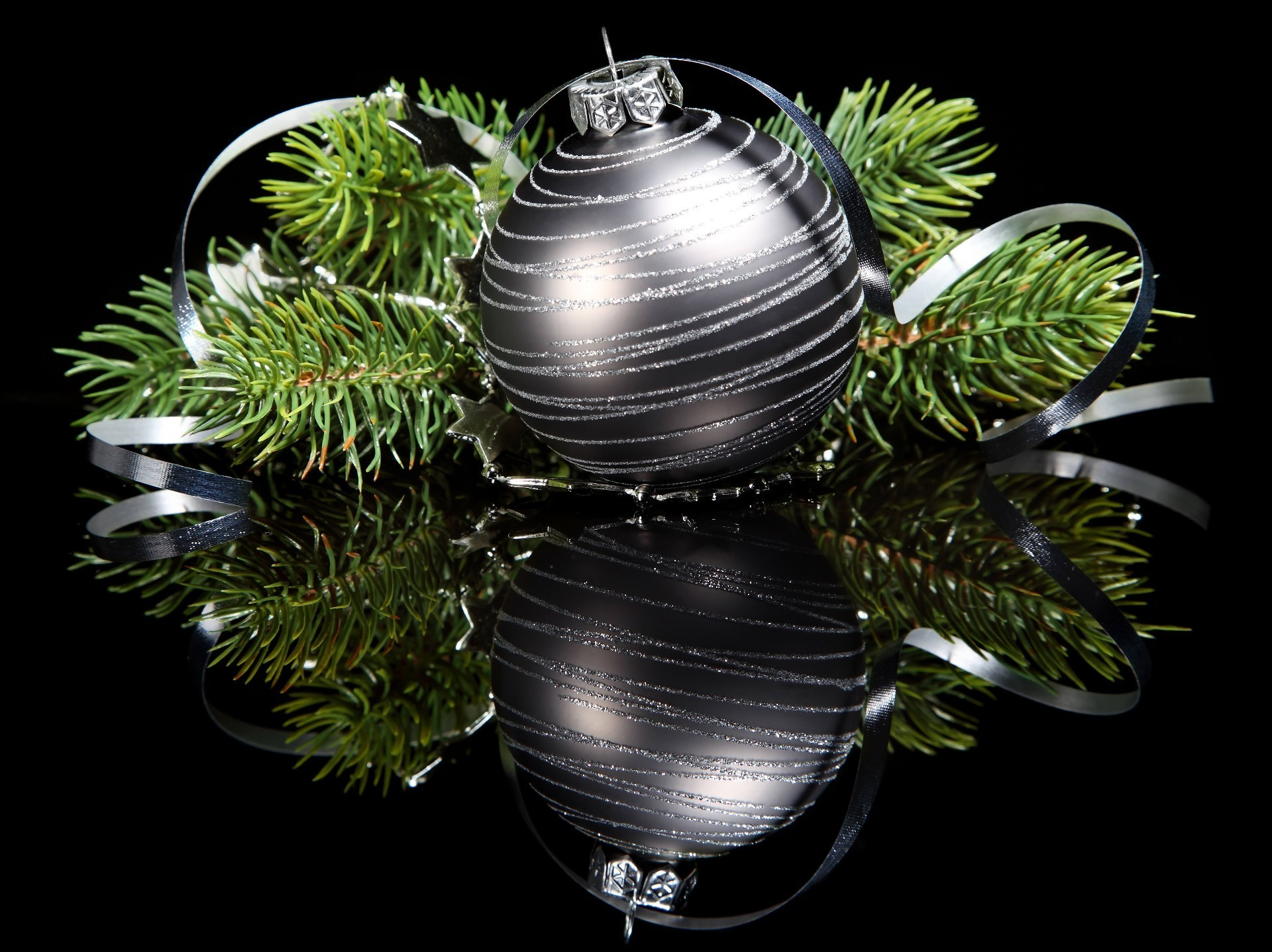 Silver Christmas ball with green branches on a black mirror