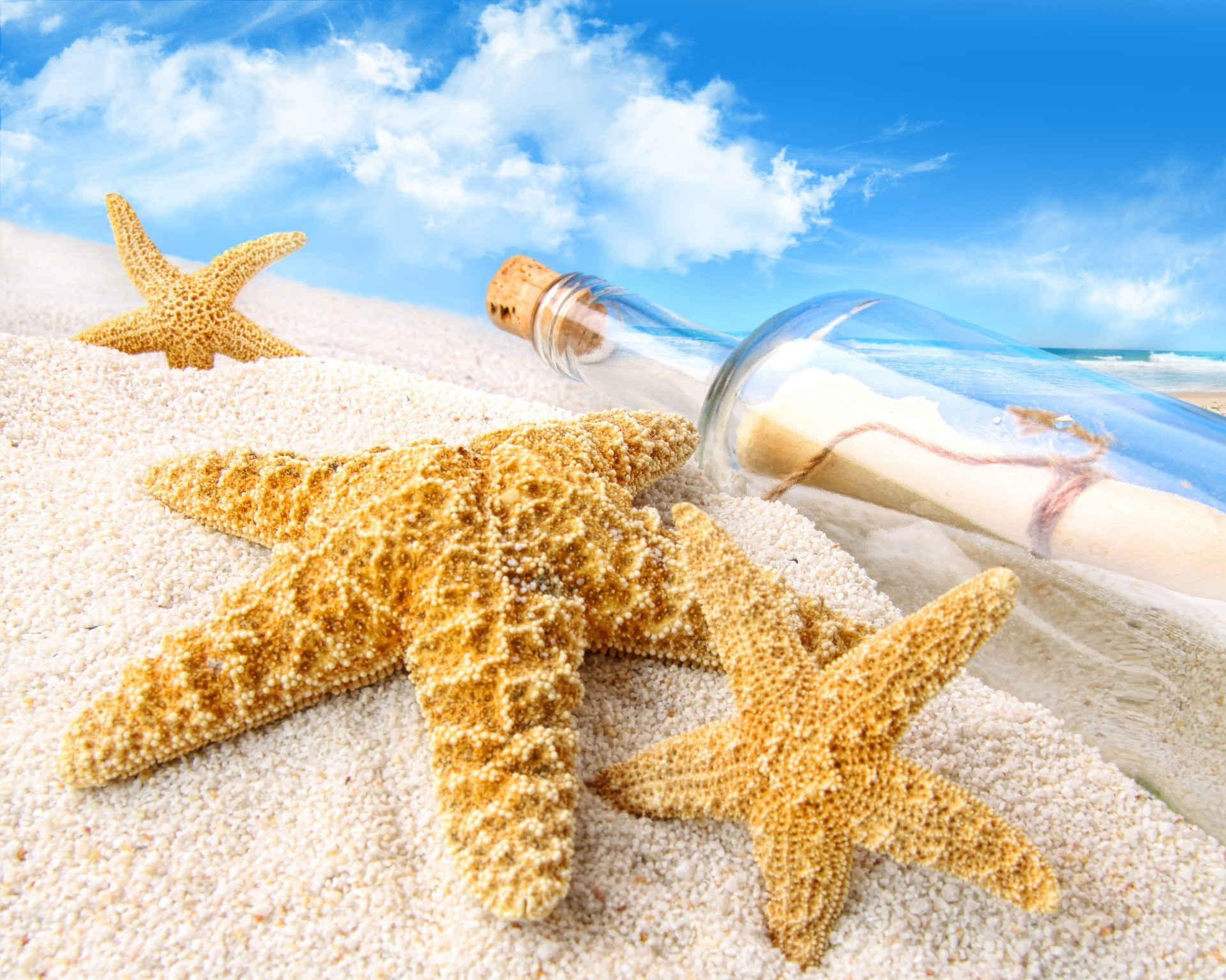 Bottle with a letter and starfish on the sand