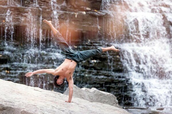 Man performs rack with one hand near the waterfall