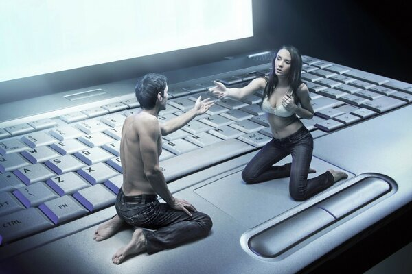 Love with couple sitting on laptop keyboard