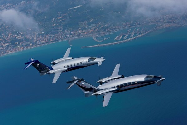 Two private aircraft fly along the coast