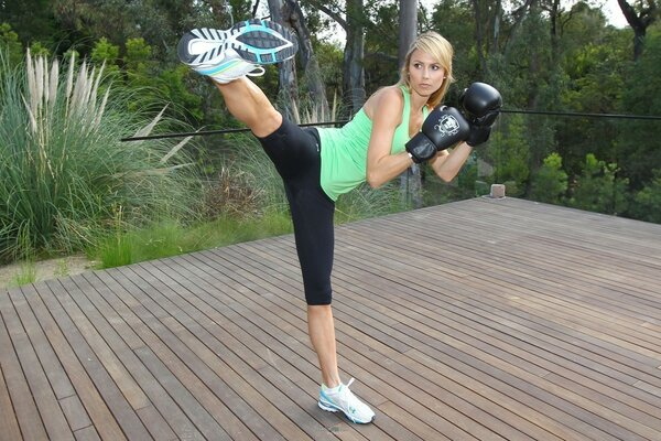 Pretty athlete doing exercises, performing leg swings