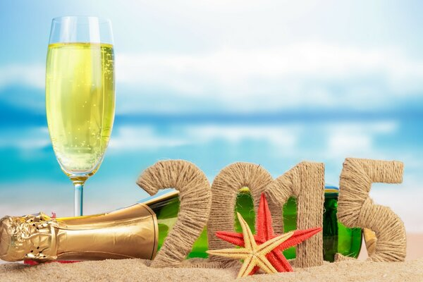 A bottle of champagne, a glass, starfish on sandy beach