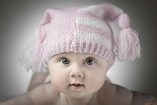 Cute little baby in pink hat looks great in