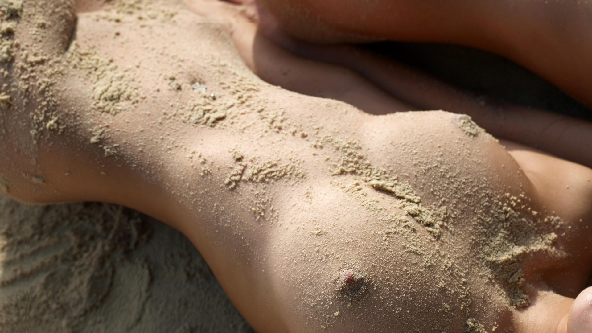 Naked female body in the sand