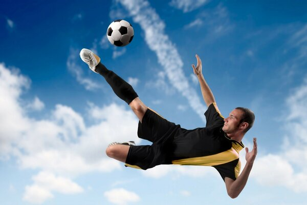 Football Player Kicking The Ball in Mid Air